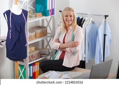Beautiful woman looking at camera, standing near the table in the workshop with clothes.