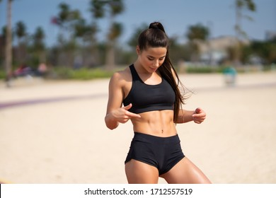 Beautiful woman looking down at her firm stomach and muscular abs results of exercising and training hard in the gym.