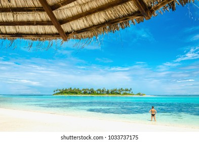 A beautiful woman is looking at an exotic uninhabited island with a sandy beach and tall palm trees with a palm tree umbrella in the foreground