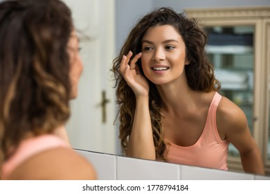 Beautiful woman looking herself in the mirror in her bathroom.