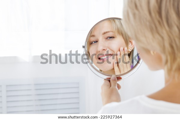 Beautiful woman looking in the mirror in the morning and smiling