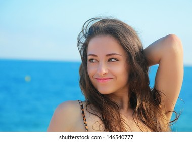 Beautiful woman looking on blue sea and sky background. Closeup portrait