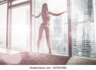 Beautiful woman looking outside the window in her beautiful apartment