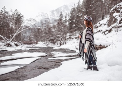 Beautiful woman looking at river covered with ice.