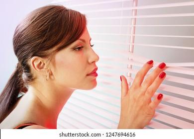 Beautiful woman is looking through jalousie, closeup