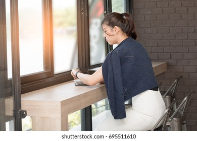 Beautiful woman looking time at watch. Waiting and sitting at cafe or restaurant. Businesswoman dressed in fashion costume. Stylish woman.