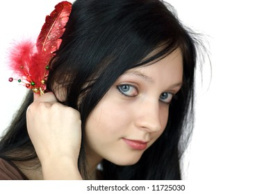 Beautiful woman looking at you holding bijouterie feather isolated on white