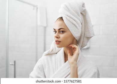beautiful woman looks at herself in a mirror and a towel on her head a bathrobe