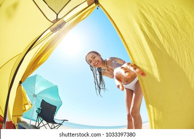 beautiful woman looks inside the tent and asks someone going outside with her . view from inside tent on the sea and sandy beach with beach umbrella and beach chair on a bright sunny day. young couple