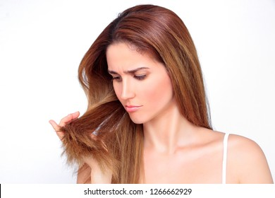 Beautiful woman looks stressed on her damaged hair
