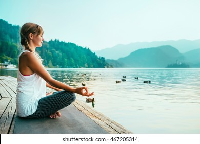 Beautiful woman in lotus position, meditating by the lake, sunset, water birds