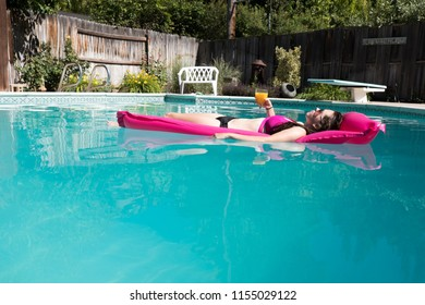 Beautiful woman lounging in an outdoor backyard swimming pool on a pink raft holding a drink in her hand on a sunny summer day. Diving board and garden in the background. Relaxing in a pool.