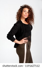 Beautiful woman with lush hair style in afro style poses on white background. The woman is dressed eclectically in leggings and a shortened jacket.