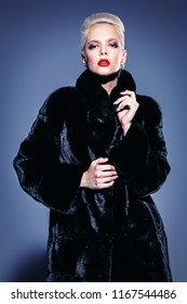 Beautiful woman in luxurious fur coat posing in studio. Luxury, rich lifestyle. Fashion shot.