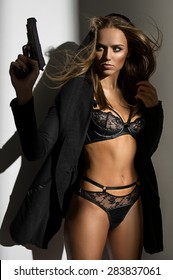 Beautiful woman in a luxurious lingerie and hood with a gun