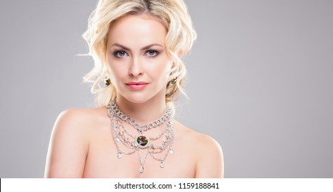 Beautiful woman in luxury jewelery. Attractive young girl wearing golden jewelry.