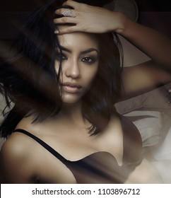 Beautiful woman lying in bed.  Studio shoot.