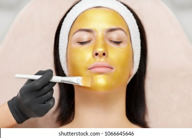 Beautiful woman lying with closed eyes and enjoying rejuvenating and moisturizing spa procedures in beauty salon. Hand of professional cosmetologist applying gold mask on client's face.