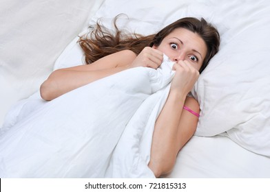 beautiful woman lying covered with a quilt in white bed and afraid