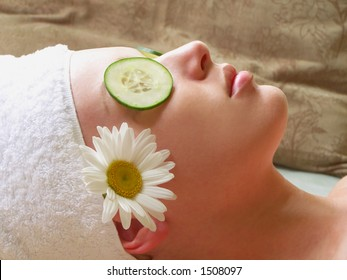 Beautiful woman lying down with cucumber slices and daisy.