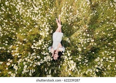 Beautiful woman lying down in daisy field