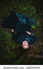 Beautiful woman lying down in forest