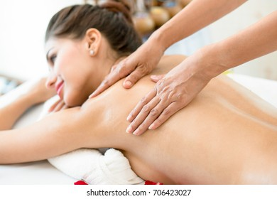 Beautiful woman lying down on the bed relax in spa salon with oil massage.