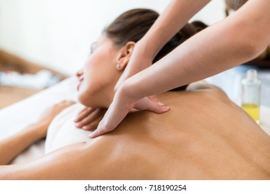 Beautiful woman lying down on the bed relax in spa salon with oil massage. selective focus  on hand.