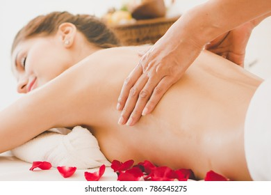Beautiful woman lying down on the bed relax in spa salon with massage.