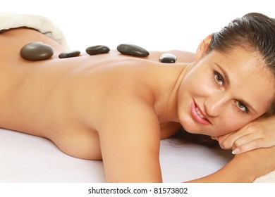A beautiful woman lying during a stone therapy isolated on white