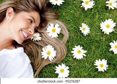 Beautiful woman lying in a garden of flowers