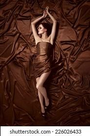 Beautiful woman lying on a chocolate fabric.