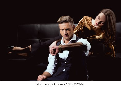 beautiful woman lying on couch while handsome man looking at watch isolated on black
