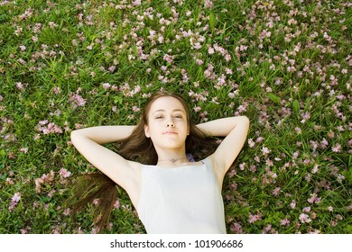 Beautiful woman lying on a garden of flowers and smiling