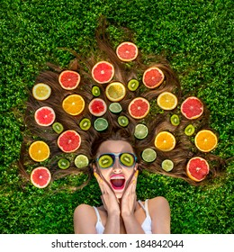 Beautiful woman lying on the grass with fruits around her hair and kiwi on her eyes