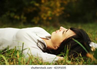 Beautiful woman lying on the green grass