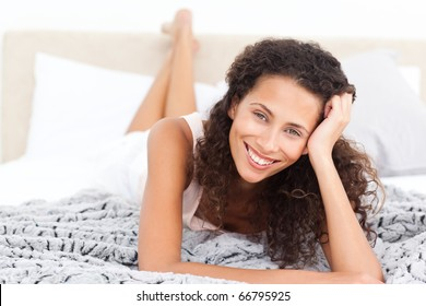 Beautiful woman lying on her bed and smiling at the camera