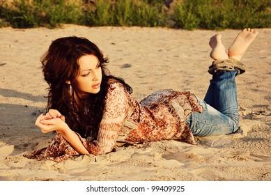 Beautiful woman lying on the sand