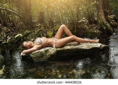 Beautiful  woman lying on the stone in the jungle during rain