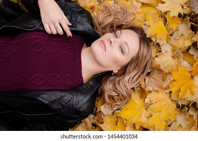 Beautiful woman lying on yellow leaves in park. Leisure time on warm autumn day