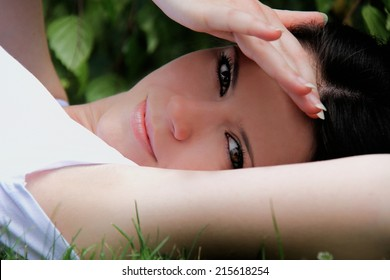 Beautiful woman is lying and resting in the grass