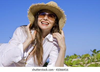 A beautiful woman lying smiling on the beach wearing hat and sunglasses