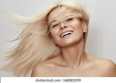 Beautiful woman with magnificent blond hair. Happy model face with windswept flying hair. Shiny long health hairstyle. Beauty and haircare