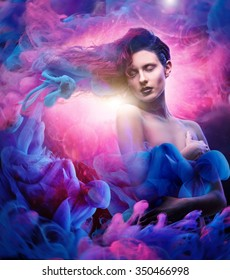 Beautiful woman with magnificent galaxy hair in blue, pink clouds with spiritual light in the middle.