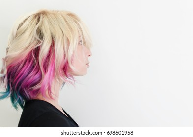Beautiful woman with magnificent galaxy hair style. New trend rainbow or unicorn haircut. Colored pastel blonde hair.