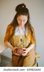 Beautiful woman makes clay pot on the pottery wheel