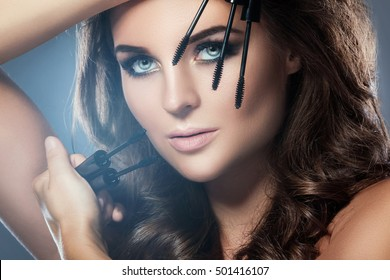 Beautiful woman with beautiful make-up applying mascara on her lashes