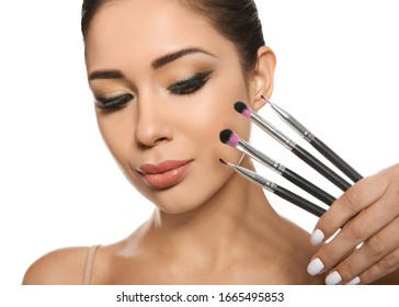 Beautiful woman with makeup brushes on white background