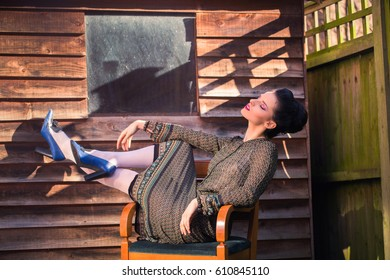 Beautiful woman with makeup and hairdo lies on a chair beside wooden house