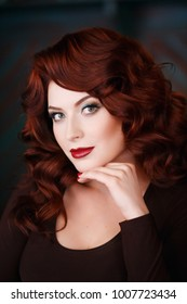 Beautiful woman with makeup, wavy and red hair, burgundy lips, looks into frame.